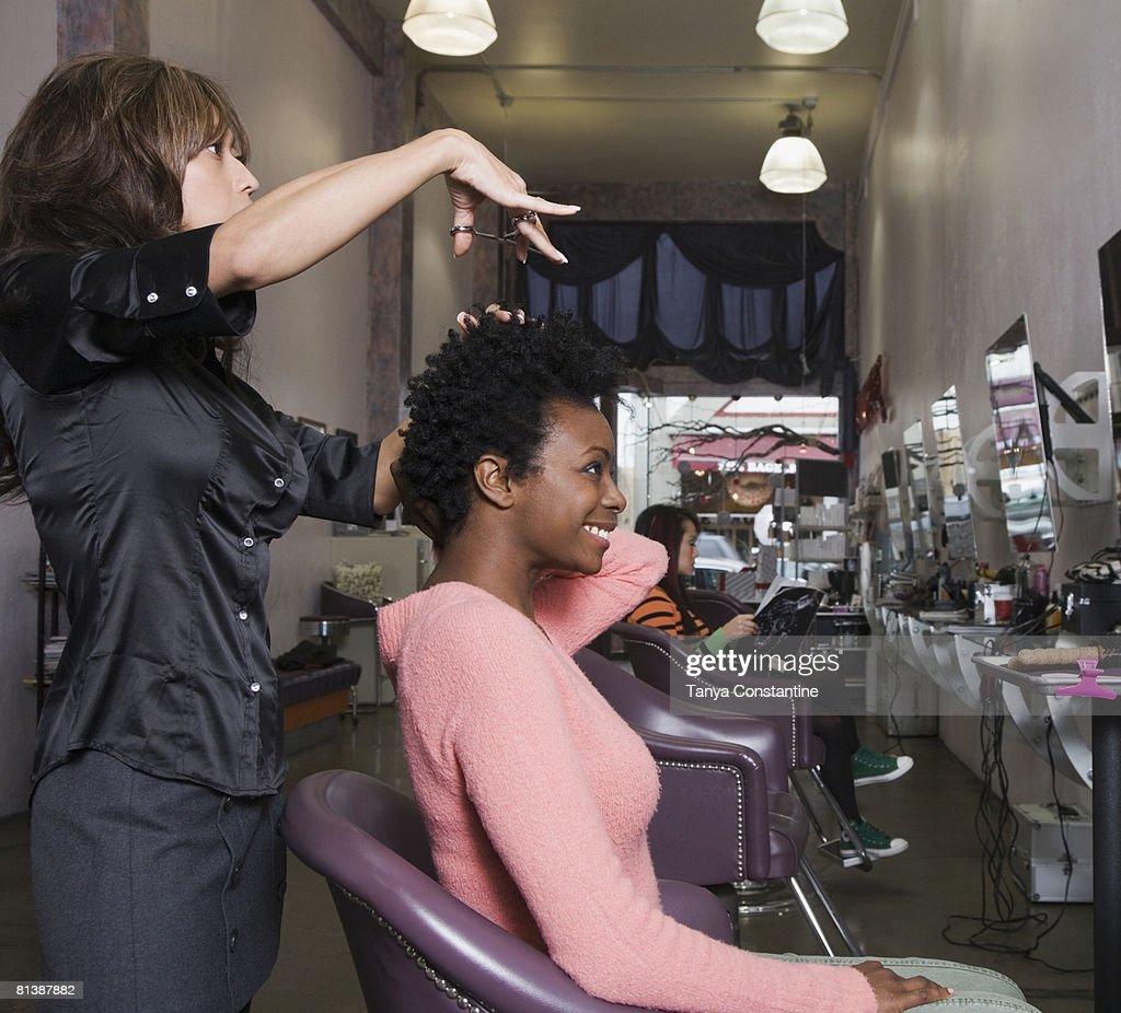 Hispanic hair stylist cutting African woman?s hair : Stock Photo