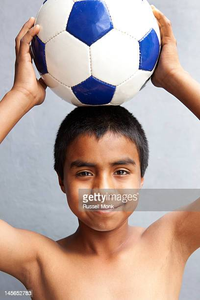 Hispanic happy kid holding a ball over his head.