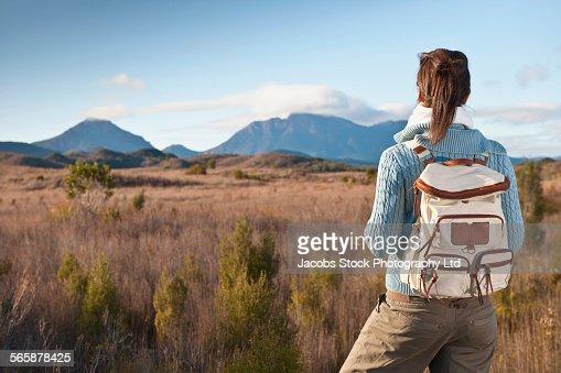 Hispanic hiker standing in remote field