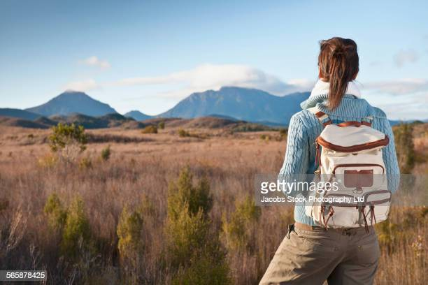 Hispanic hiker standing in remote field
