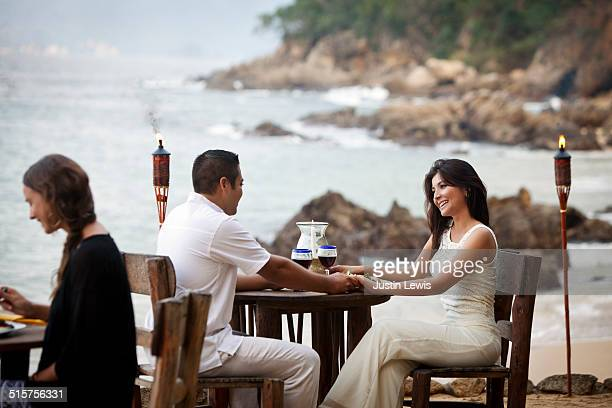 Hispanic Honeymoon Couple at Beachside Restaurant