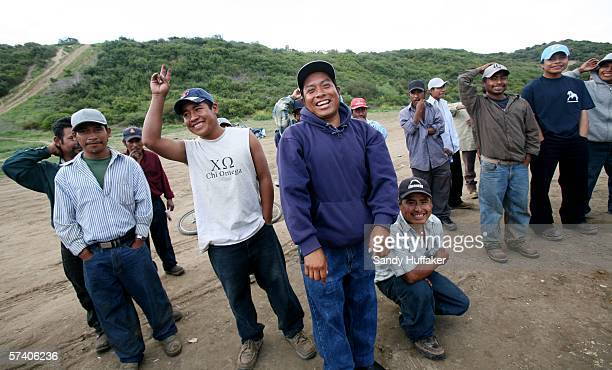 Hispanic immigrants share a laugh while waiting to receive handouts from a church group at a migrant camp April 23 2006 in Del Mar California Many...