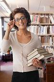 Hispanic librarian holding stack of books