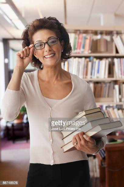 Hispanic librarian holding stack of books