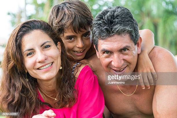 Hispanic little boy posing with his parents