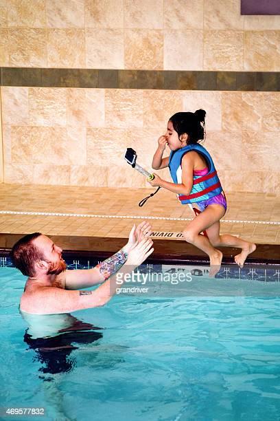 Hispanischen Mädchen springen in Pool, Vater Selfie-Stick