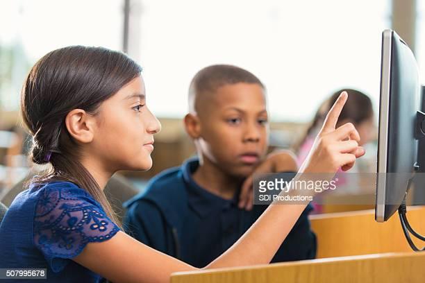 Hispanic little girl using computer in public school with classmate