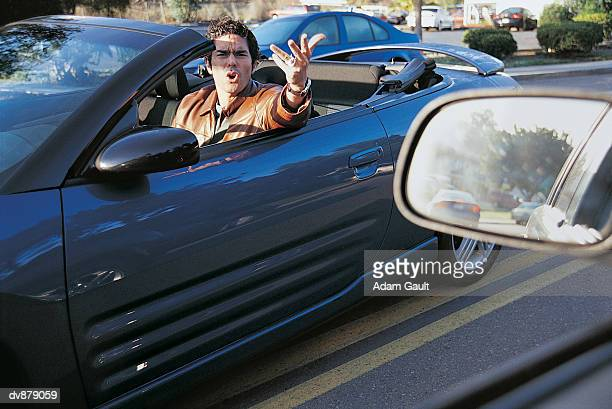 Hispanic Male Driving a Convertible Shouting at Another Car