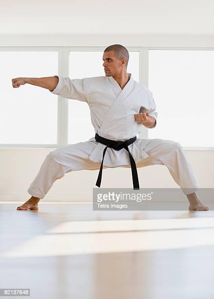 Hispanic male karate black belt in fighting stance