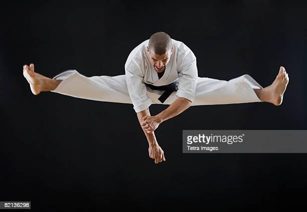 Hispanic male karate black belt jumping in air