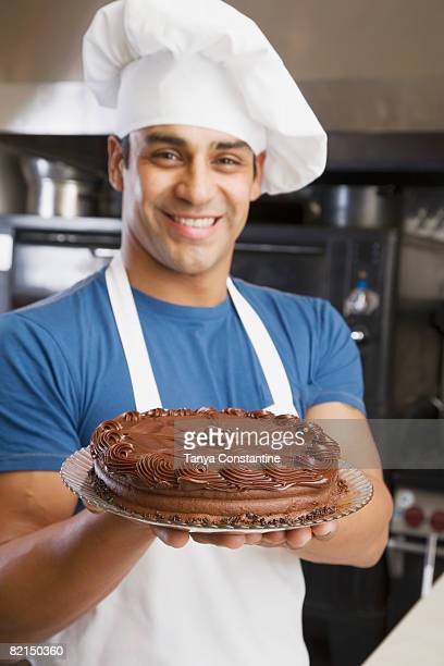 Hispanic male pastry chef holding cake