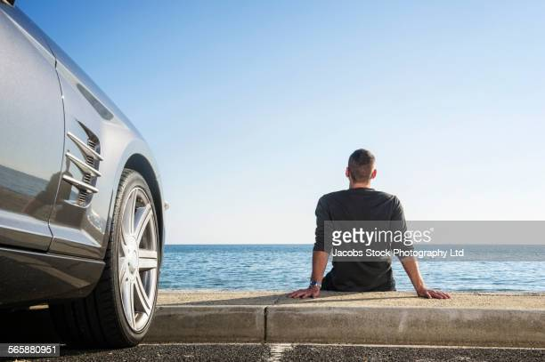 Hispanic man admiring beach near car in parking lot