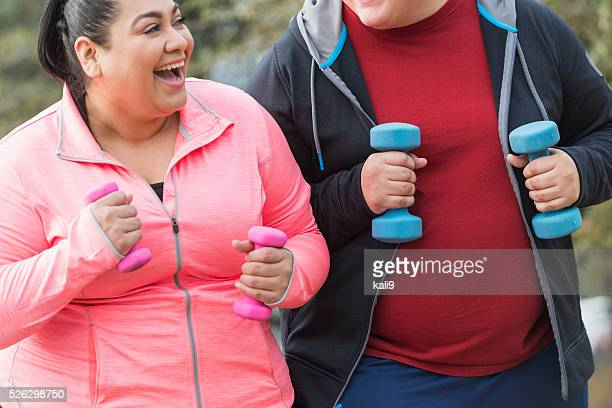 Hispanic man and woman exercising with dumbbells