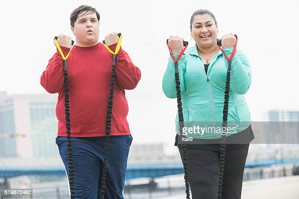 Hispanic man and woman exercising with resistance bands