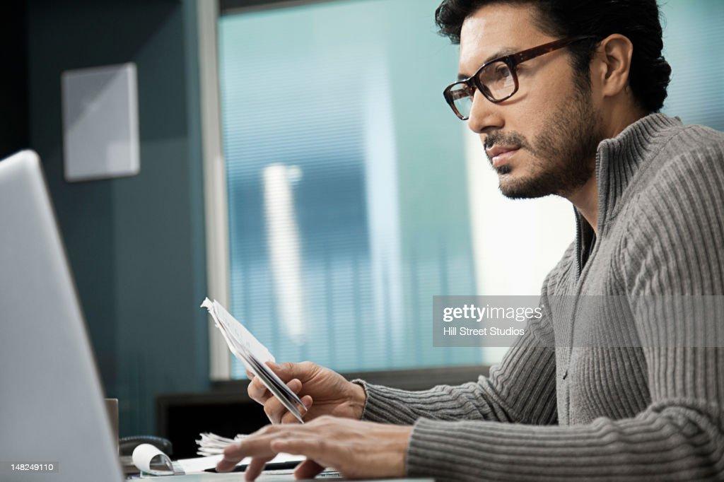 Hispanic man at desk using laptop : Stock Photo