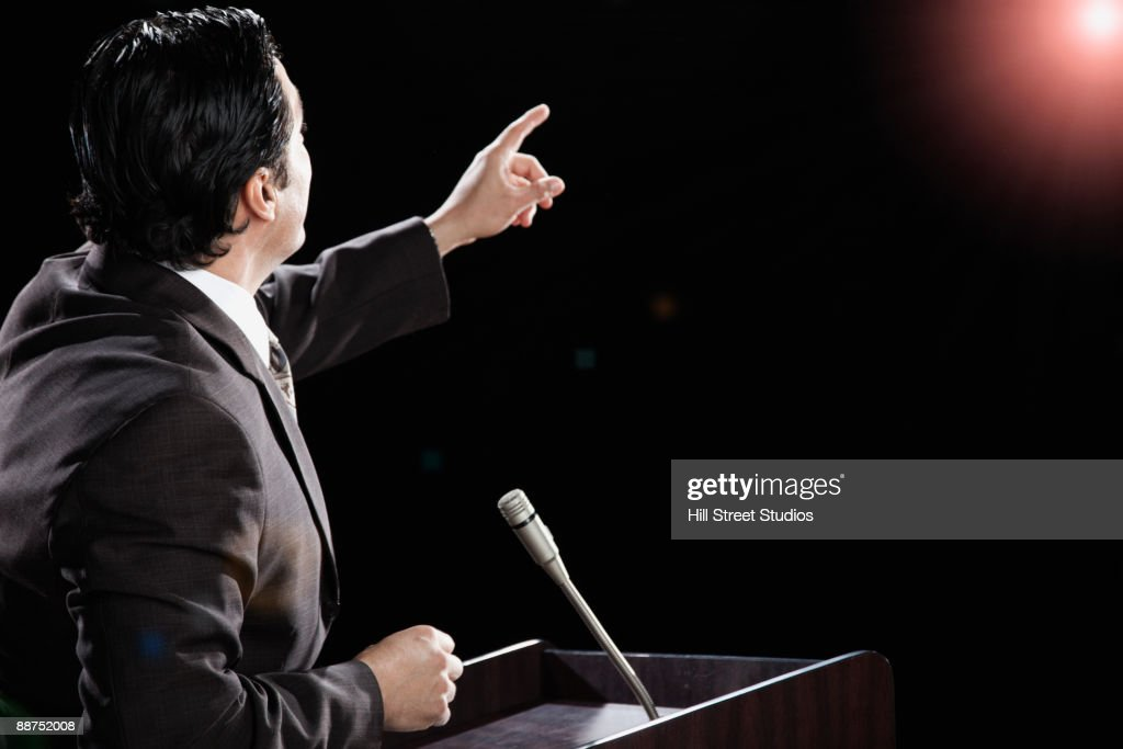 Hispanic man at podium with arm raised : Stock Photo