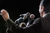 Hispanic man at press conference microphones