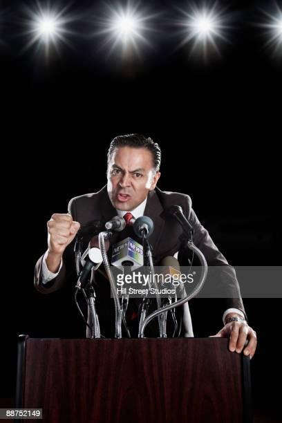 Hispanic man at press conference podium gesturing angrily