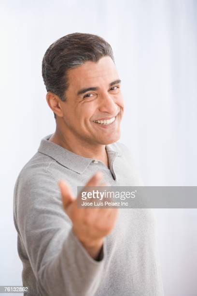 Hispanic man beckoning with hand