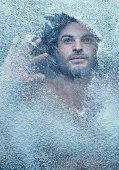 Hispanic man behind snow covered window