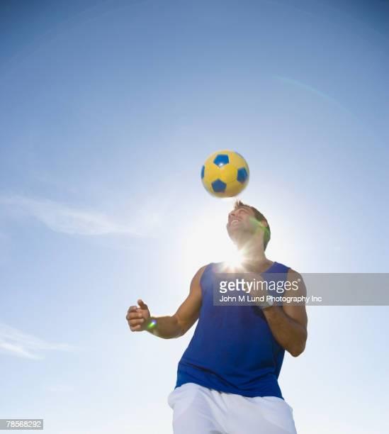 Hispanic man bouncing soccer ball on head