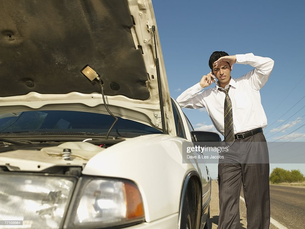 Hispanic man broken down on side of road : Stock Photo