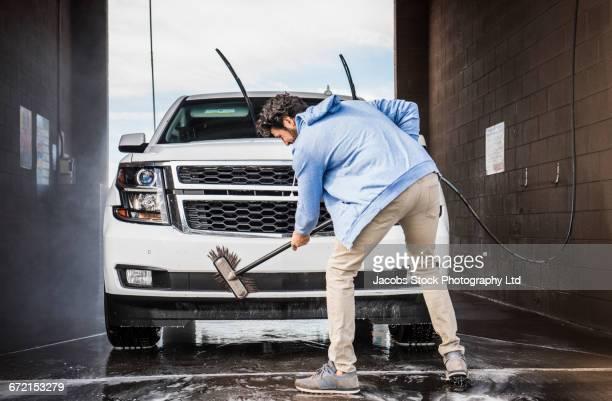 Hispanic man brushing car at self-serve car wash