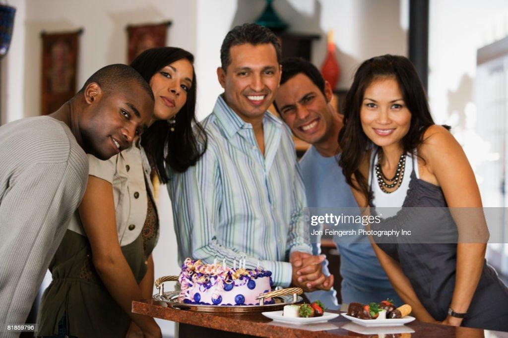 Hispanic man celebrating birthday with multi-ethnic friends : Stock Photo