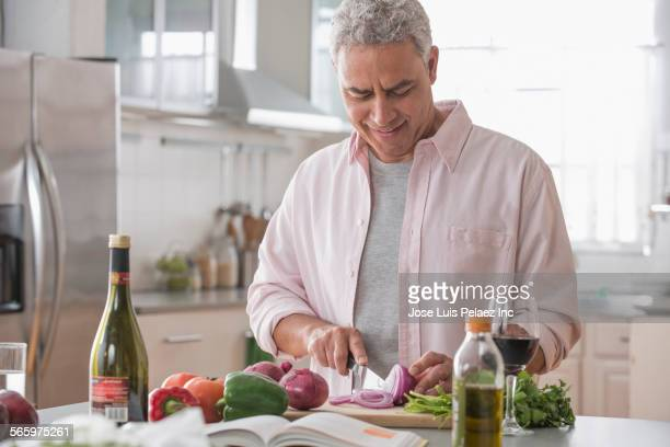 Hispanic man chopping vegetables in kitchen