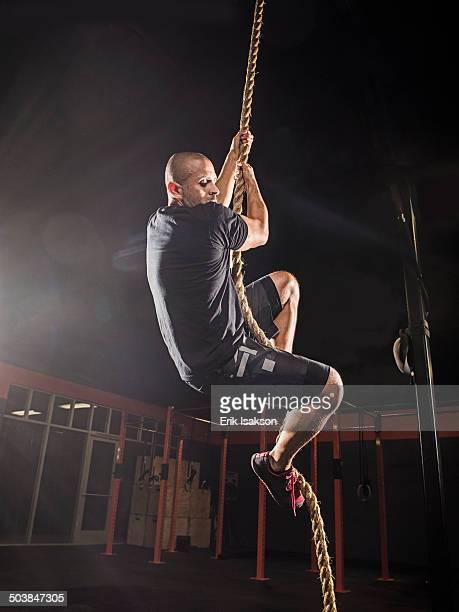 Hispanic man climbing rope in gym