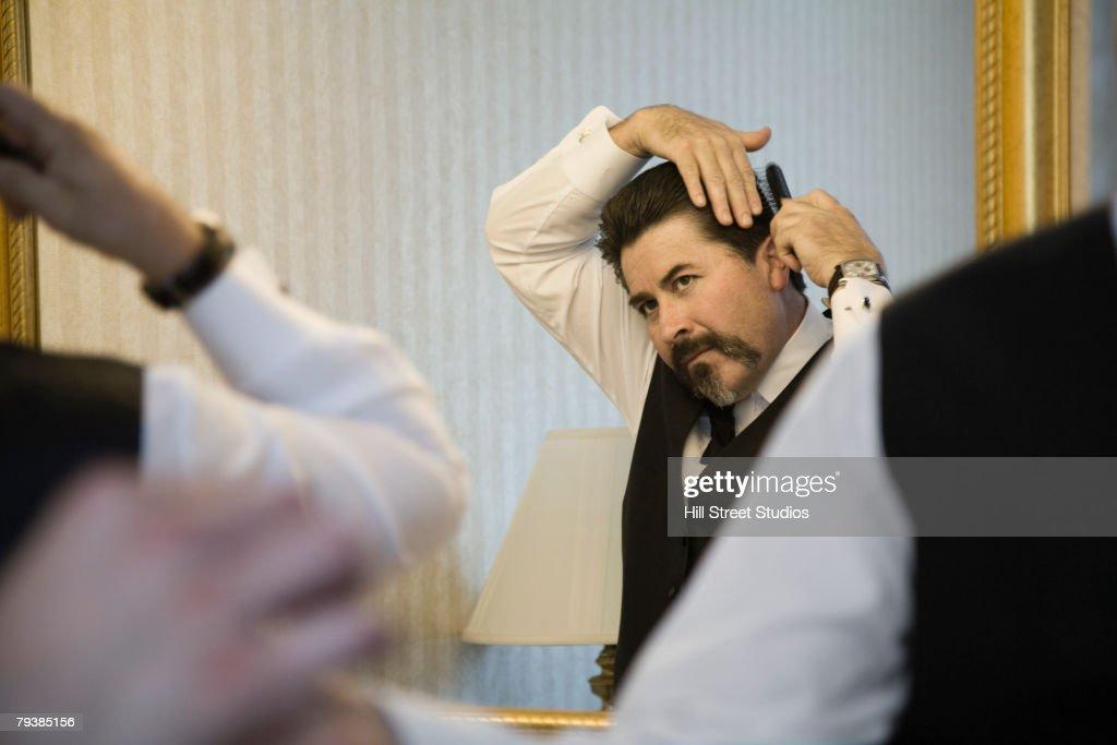 Hispanic man combing hair : Stock Photo