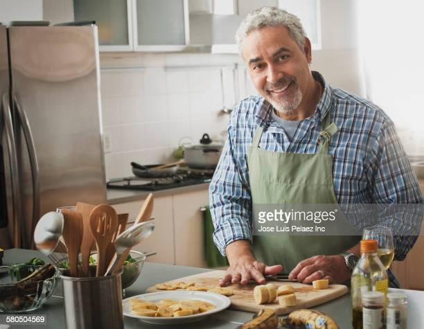 Hispanic man cooking in kitchen