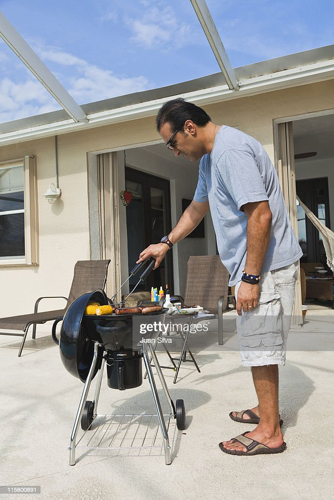 Hispanic man cooking with grill outdoors : Stock Photo