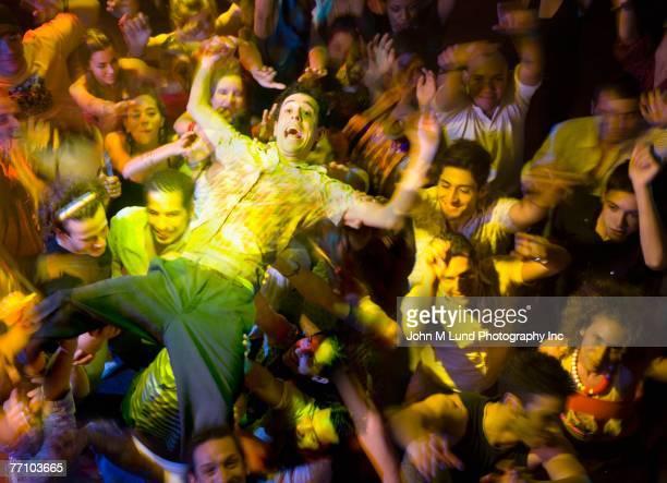 Hispanic man crowd surfing at nightclub