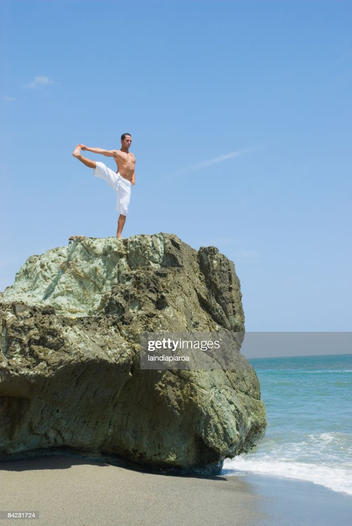Hispanic man doing yoga at beach : Stock Photo