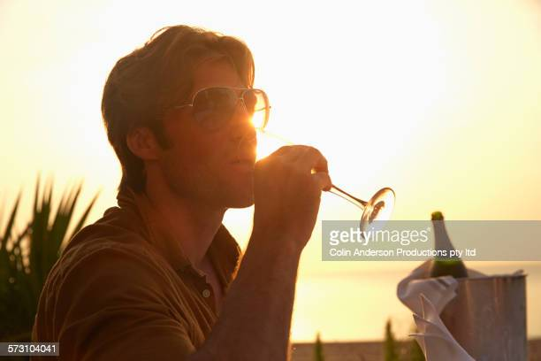 Hispanic man drinking champagne at sunset dinner outdoors