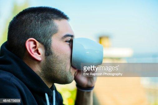 Hispanic man drinking cup of coffee : Stock Photo
