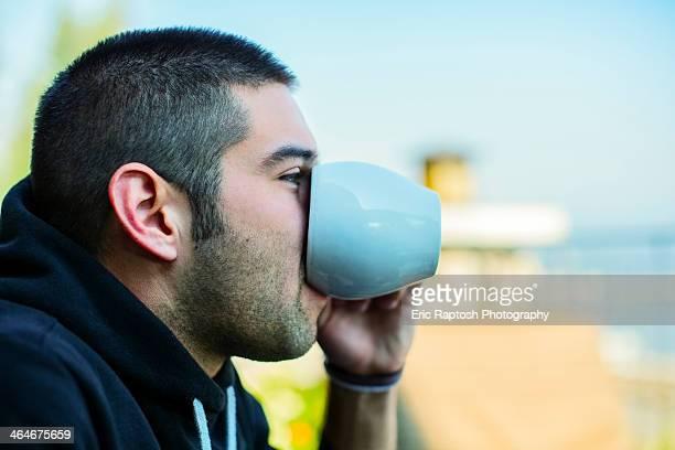 Hispanic man drinking cup of coffee