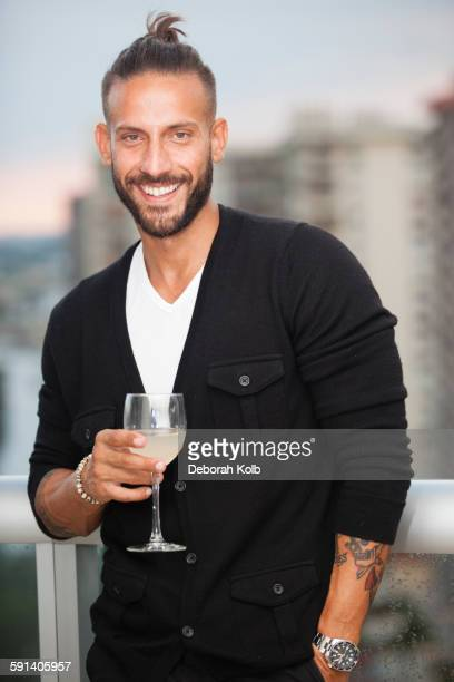 Hispanic man drinking wine on urban balcony