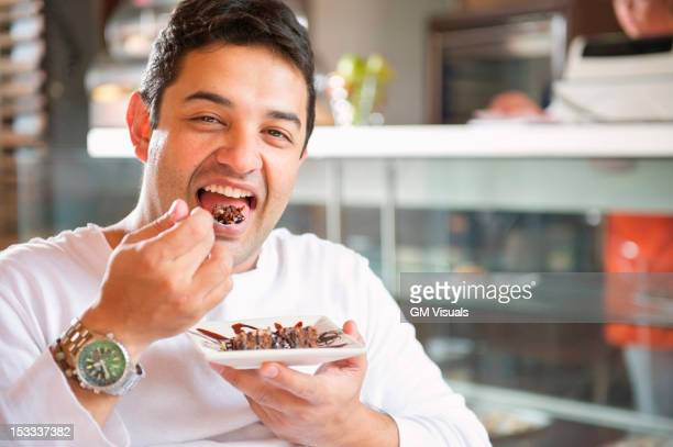 Hispanic man eating dessert in cafe
