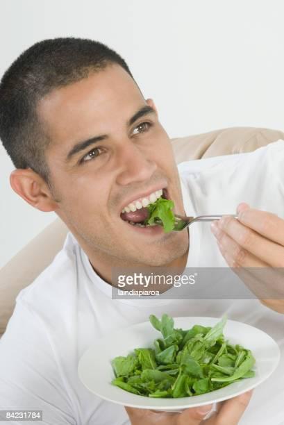 Hispanic man eating salad
