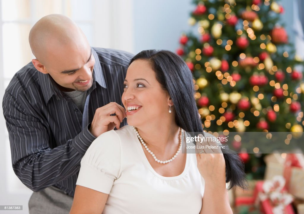 Hispanic man fastening necklace for wife : Stock Photo