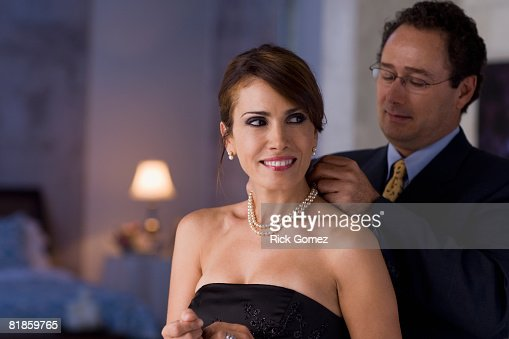 Hispanic man fastening wife?s necklace