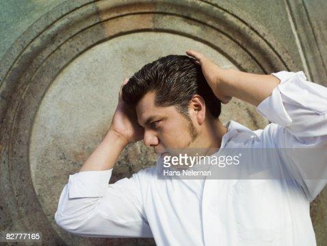 A hispanic man fixing his hair