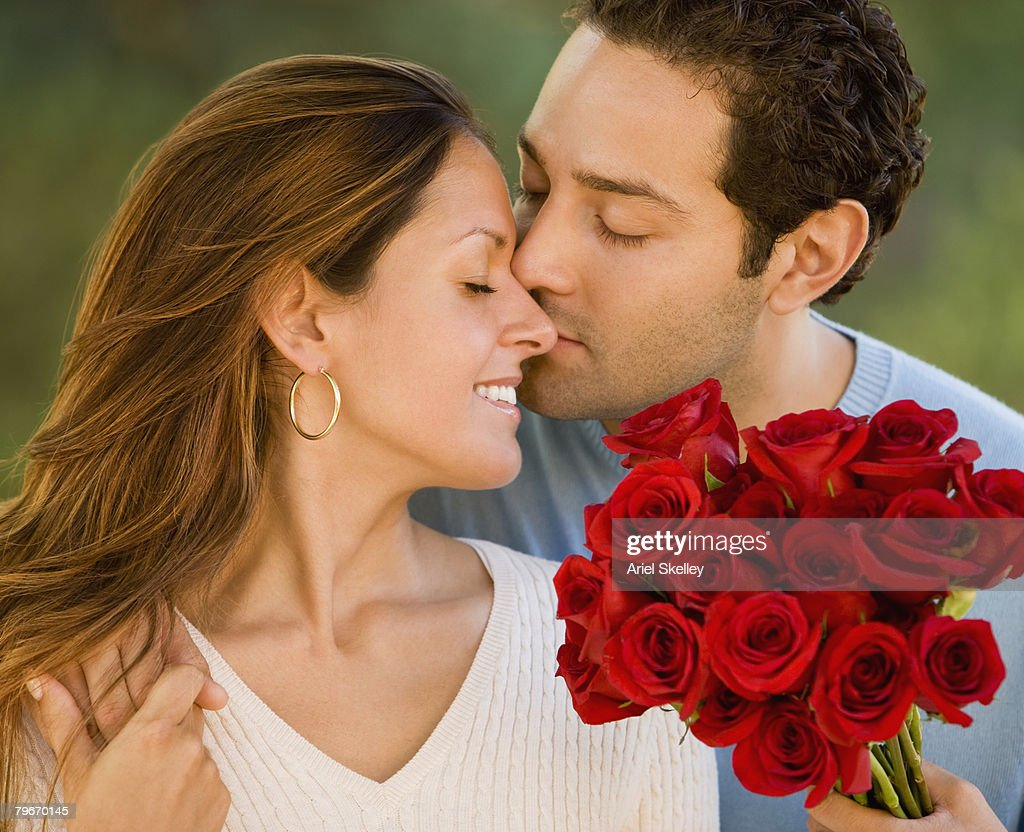 Hispanic man giving flowers to wife : Stock Photo