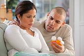 Hispanic man giving medicine to his wife