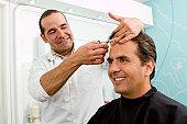 Hispanic man having hair cut in barber shop