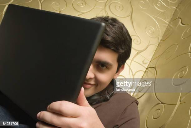 Hispanic man hiding behind laptop