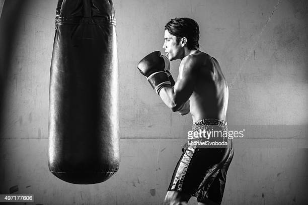 Hispanic Man Hitting a Punching Bag in Black and White