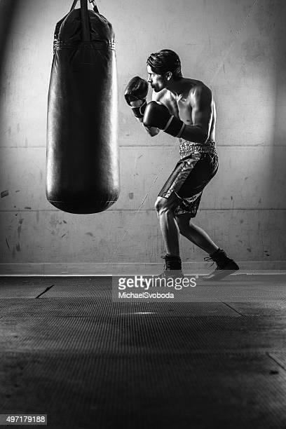 Homme hispanique frapper le sac de boxe noir et blanc